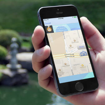 SnapMeet app shown running on iPhone 5S in a Japanese garden